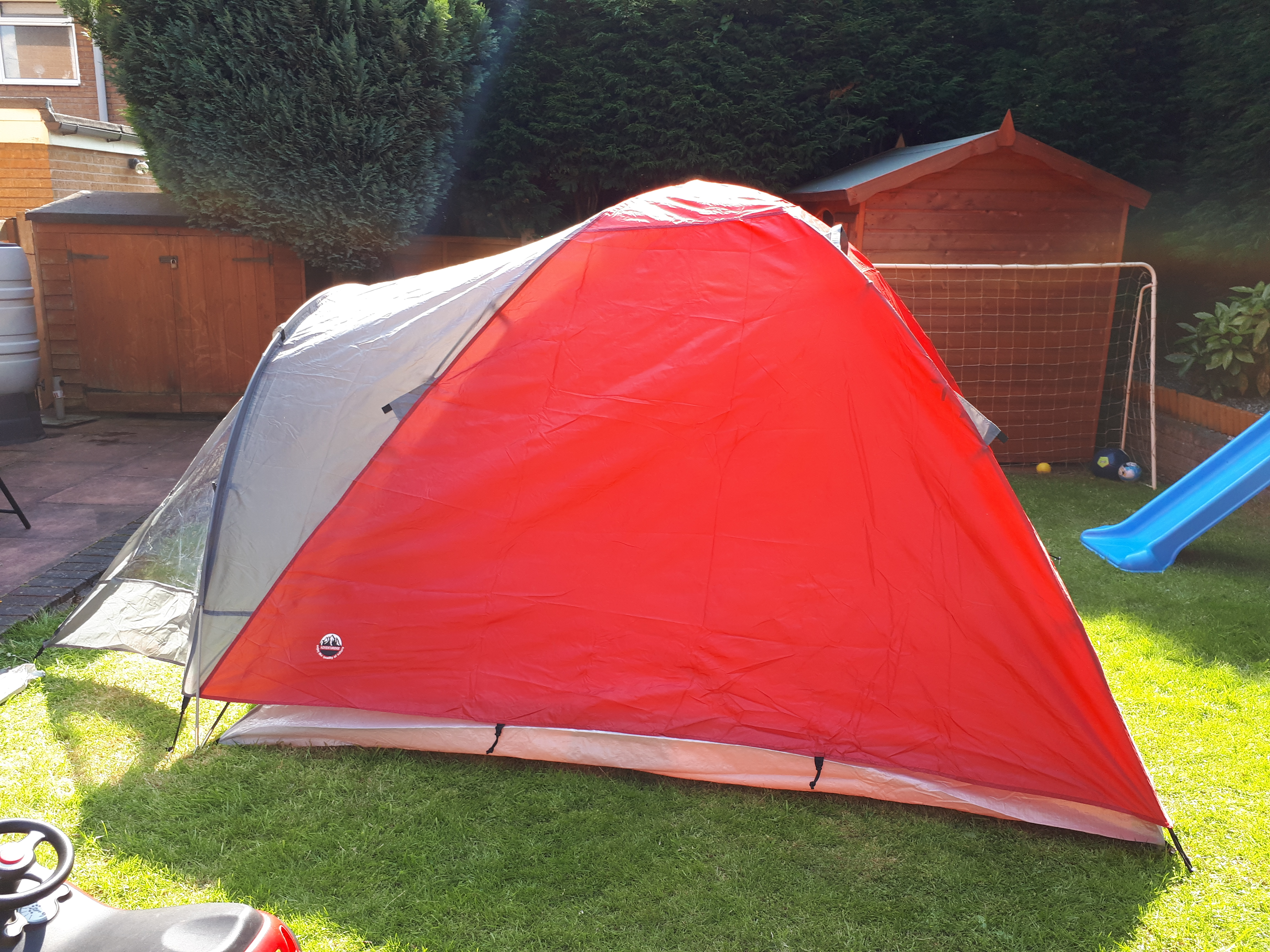 Red tent pitched in a small back garden