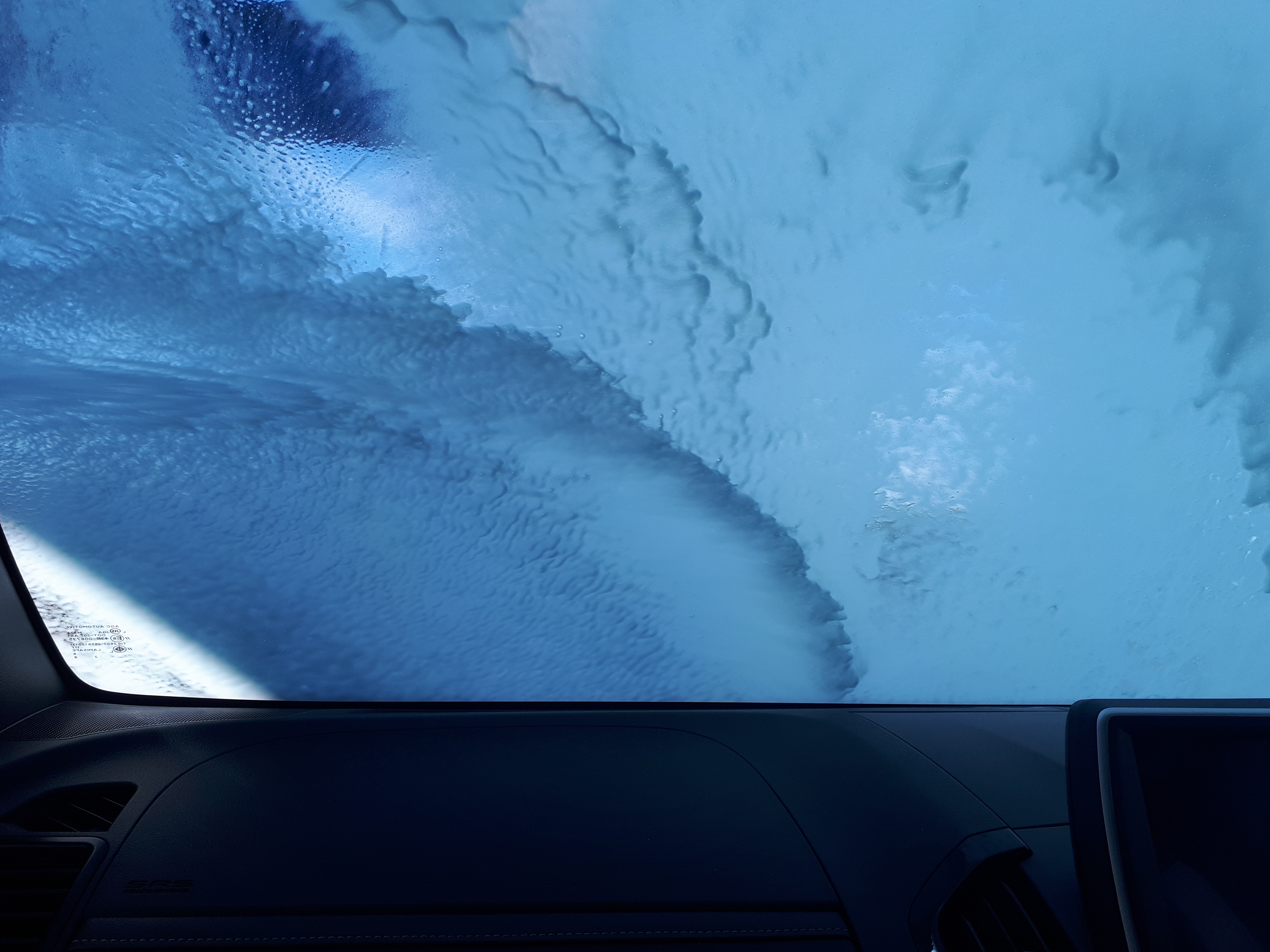 Truck windscreen covered with soap inside carwash