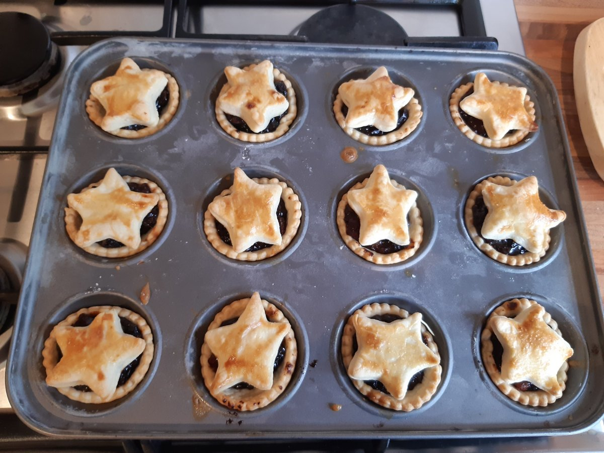 12 mince pies in a tray with star lids, glazed with egg wash, made with homemade mincemeat