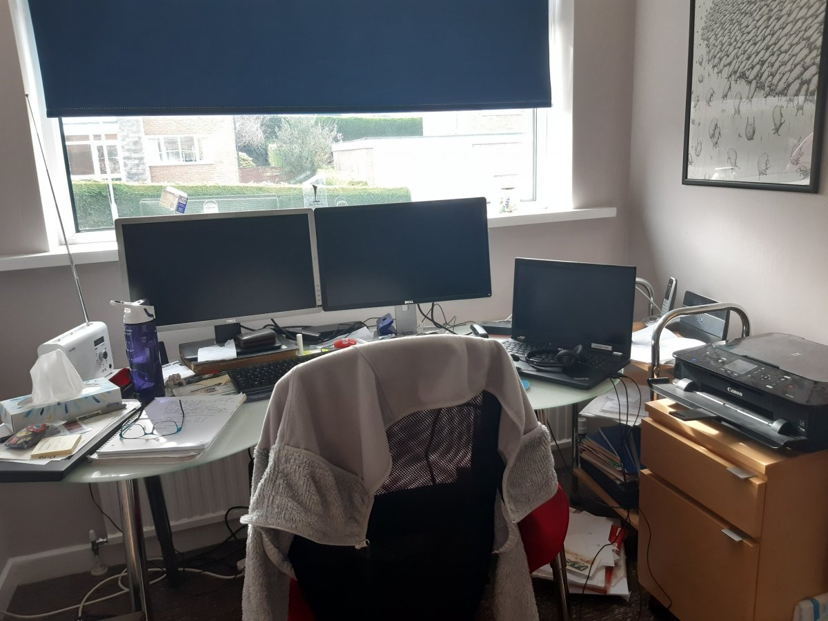 home working set up, two monitors, laptop, printer, lots of mess, water bottle and jumper