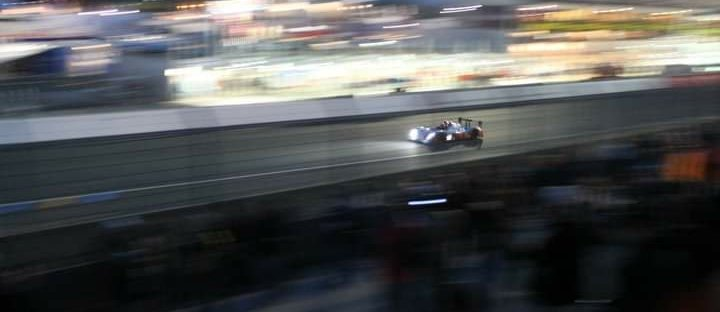 LMP1 car through the pit straight at night at Le Mans
