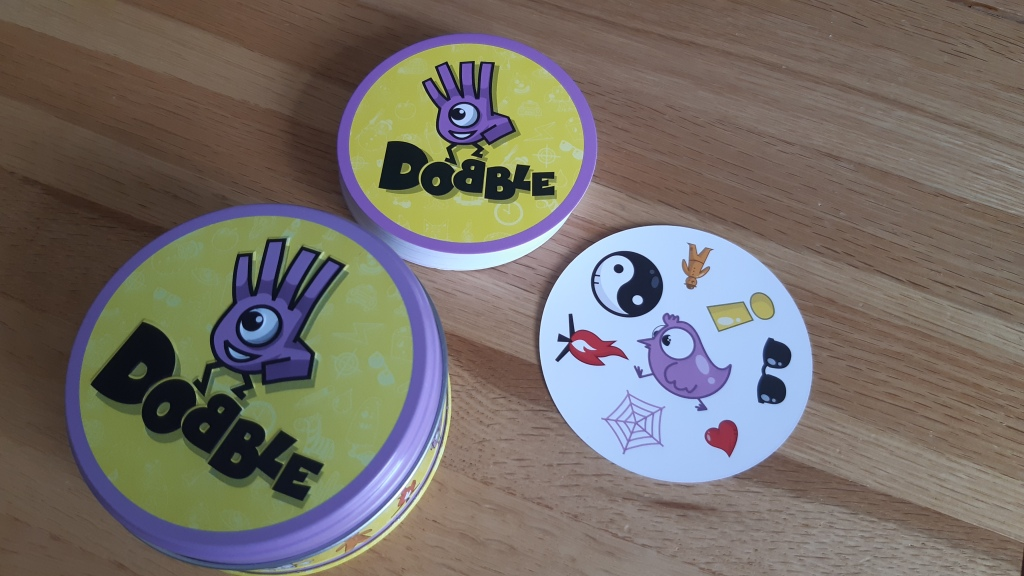 Dobble tin, card stack and a playing card
