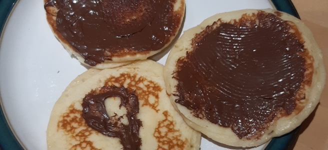 three pancakes with chocolate spread, one with a 9