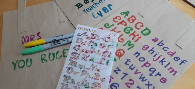 Paper bags decorated with stencilled letters and messages for teachers